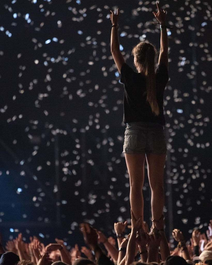 Standing woman being lifted up by her ankles at a concert in Cluj-Napoca, Romania with confetti falling all around her.