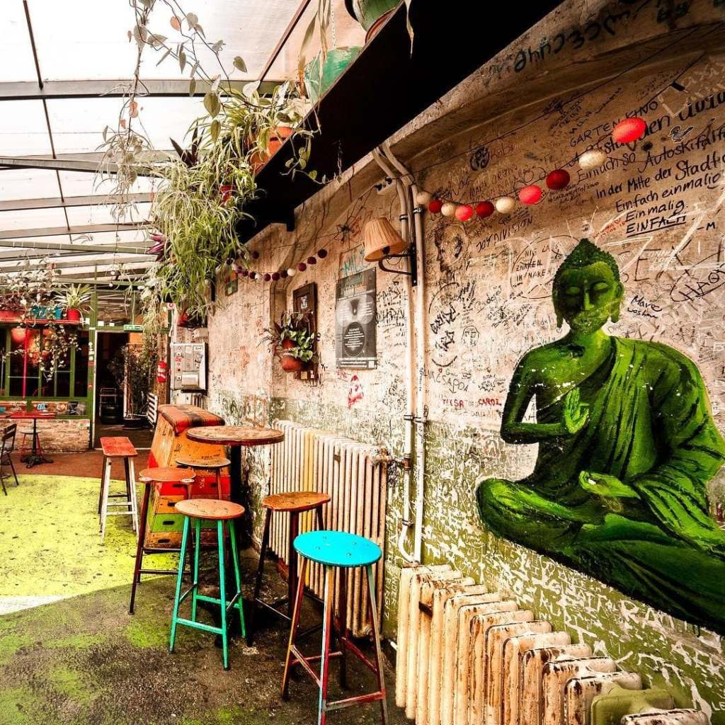 One of Budapest's iconic Ruin Bars with a green print of Buddha on the wall and multi-colored stools.