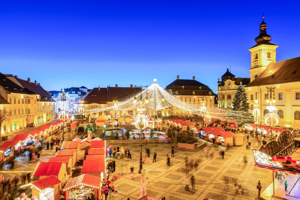 Piata Mare in Sibiu adorned with thousands of lights and Christmas booths selling things during the annual Christmas Market.