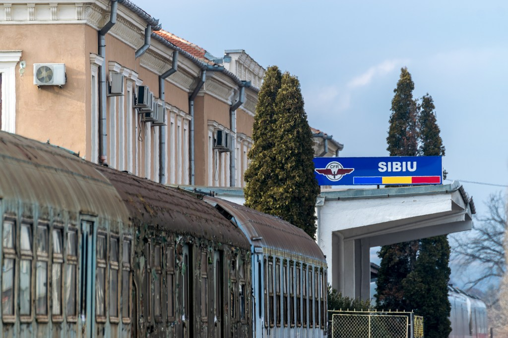 Sibiu Railway Station from the exterior and sign with Romanian flag colors.