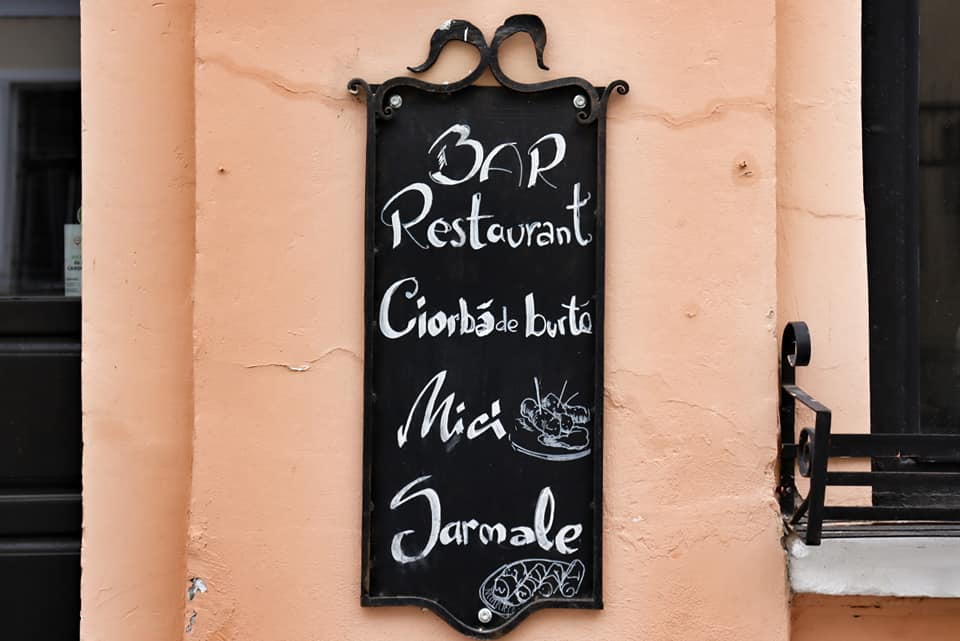Exterior facade of Casa Veche restaurant in Cluj-Napoca, Romania.  Pale pink building with a black chalkboard and daily specials listed in white.