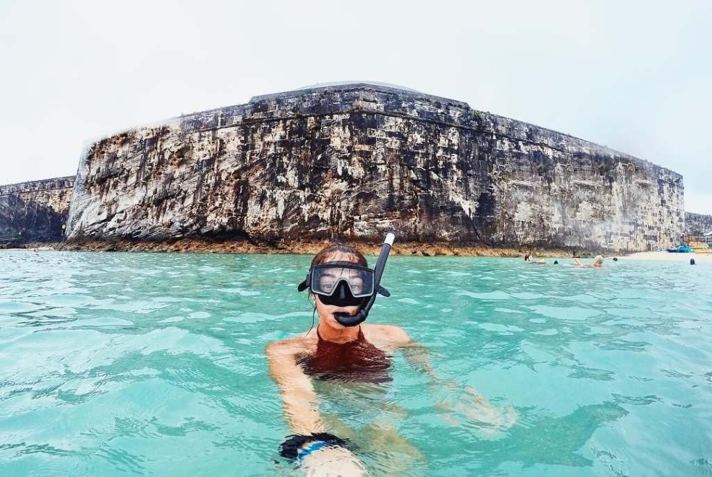 Woman taking a selfie above water in snorkel gear in Bermuda with a large rock formation behind her