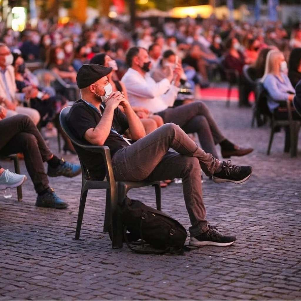 Large crowd of people sitting socially-distanced wearing masks during the annual TIFF festival in Cluj-Napoca, Romania.
