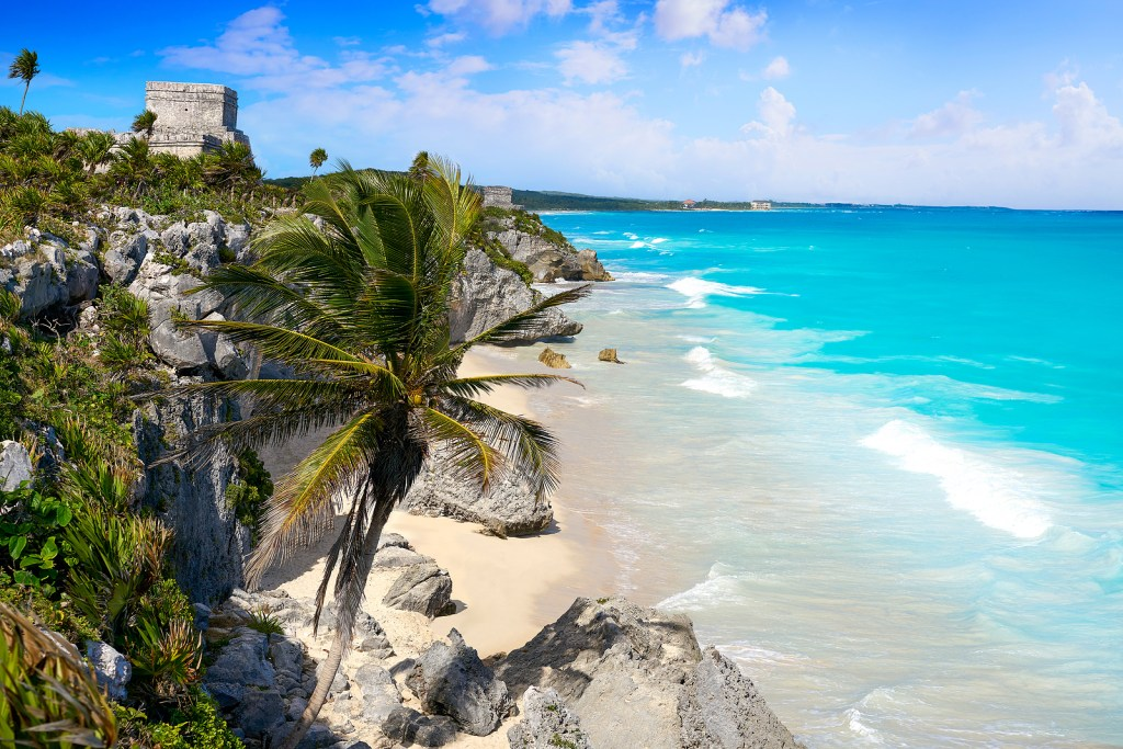 Turquoise waters of Tulum, Mexico washing up on the rocky shore.  Palm trees and Maya ruins are seen on the beaches.