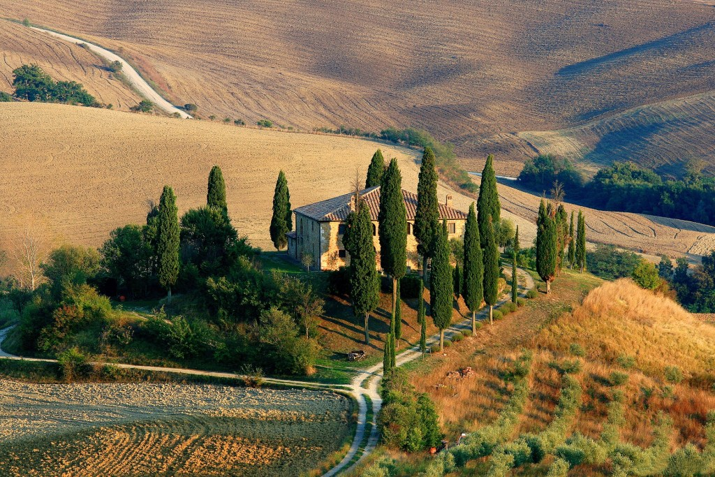 A lone villa in the hills of Tuscany surrounded by trees and golden fields.