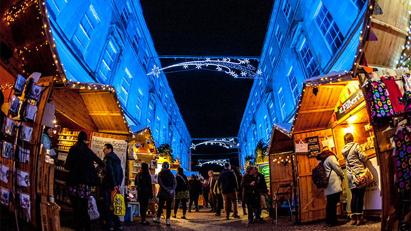 Wooden stalls are filled with shoppers beneath buildings glowing in blue light during the annual Christmas market in Bath, England.