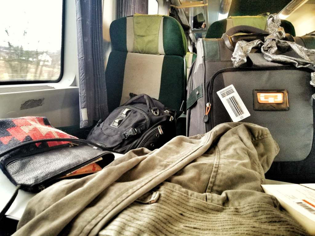 Train seats filled with belongings, clothing, and suitcases en route from Budapest to Sibiu.