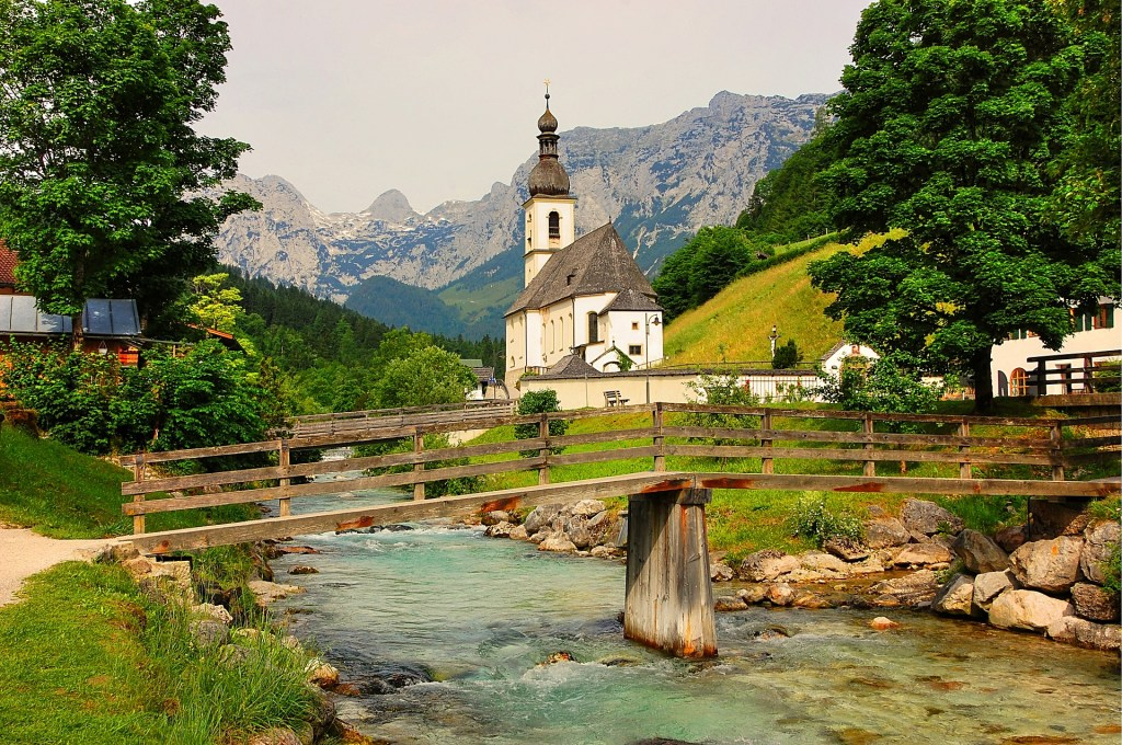 Small wooden bridge over river in German national park with little church and alps in the background.