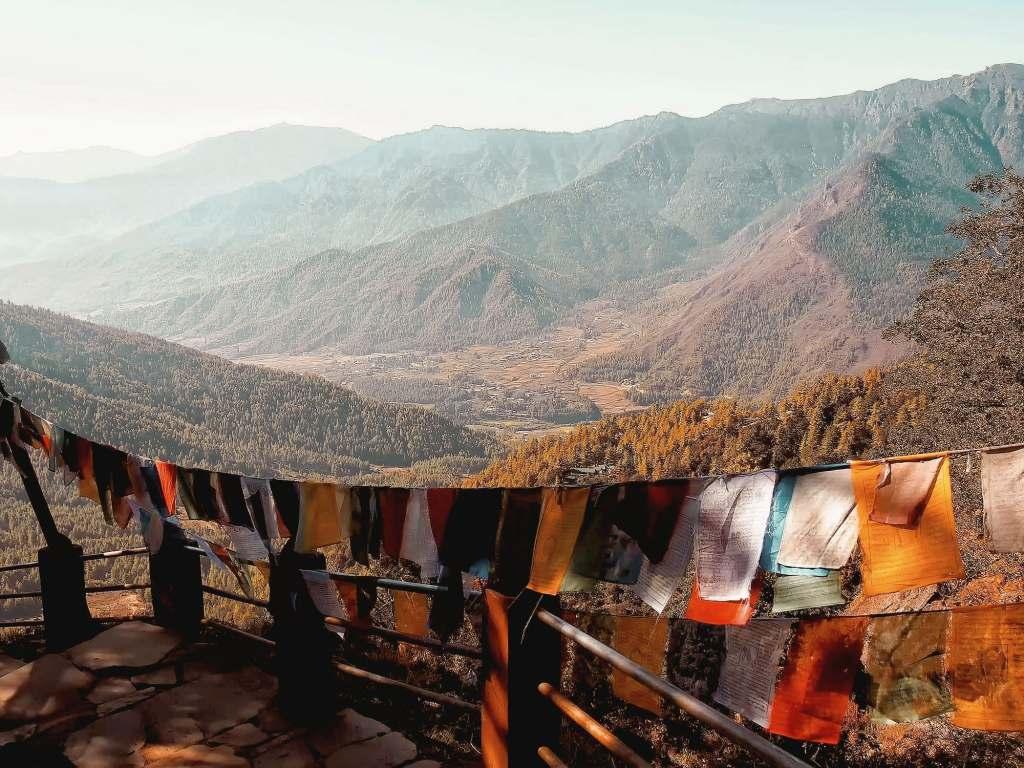 Tibetan prayer flags hanging on small patio overlooking mountains in Bhutan.