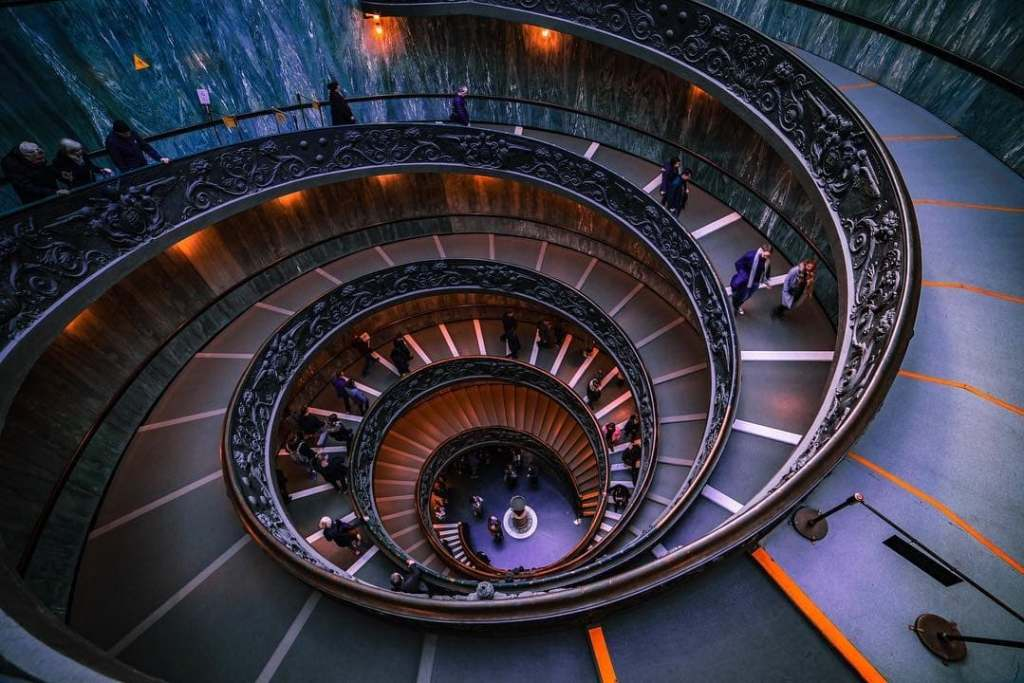 Bramante staircase at the Vatican Museum, one of the most Instagrammable places in Rome.  Colors are edited in purple and orange.