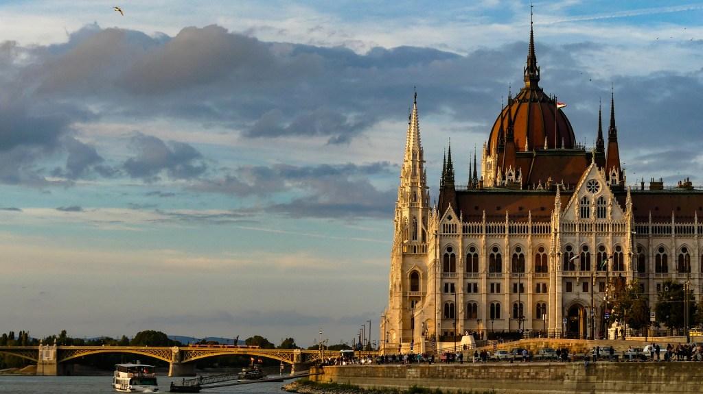 Budapest Parliament building seen beneath a cloudy sky at dusk.