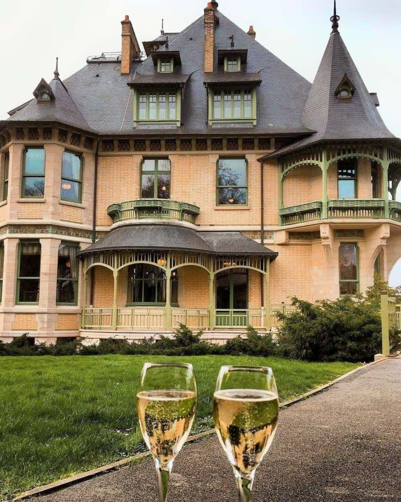 Two champagne glasses clinking in front of quaint champagne house in Reims, France.
