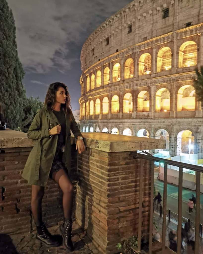 Woman standing by the Colosseum wall at night looking down at the street in Rome.