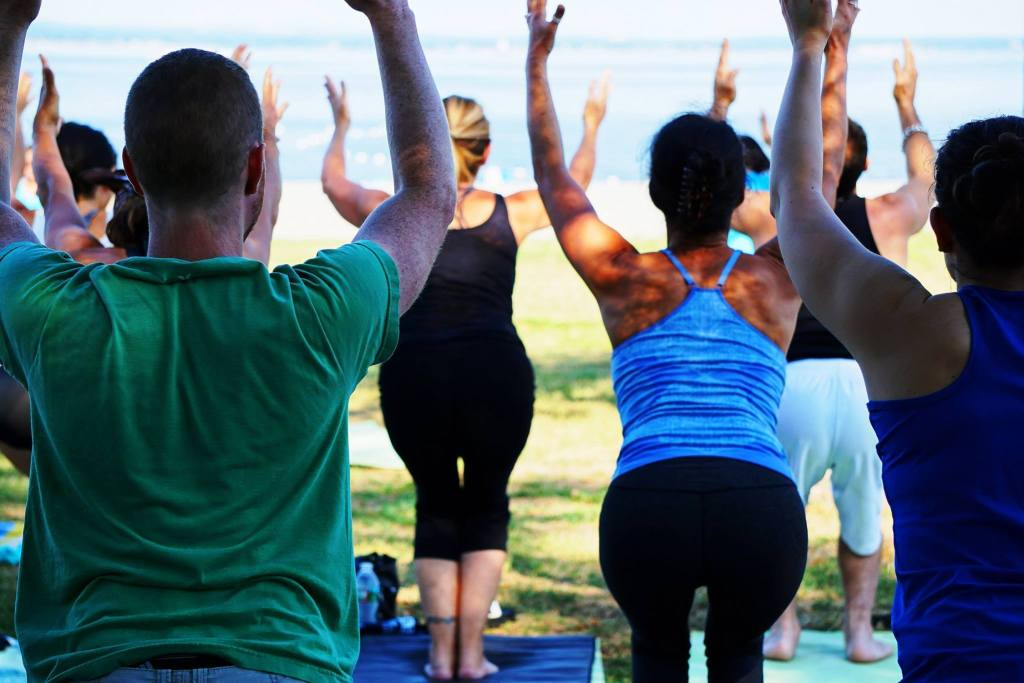 view from behind of a group of people doing yoga lakeside in chair pose.