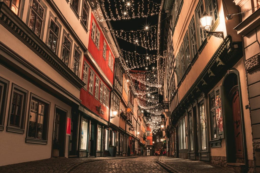 An empty cobblestone street in Erfurt, Germany lined with Christmas lights during the town's annual holiday markets.