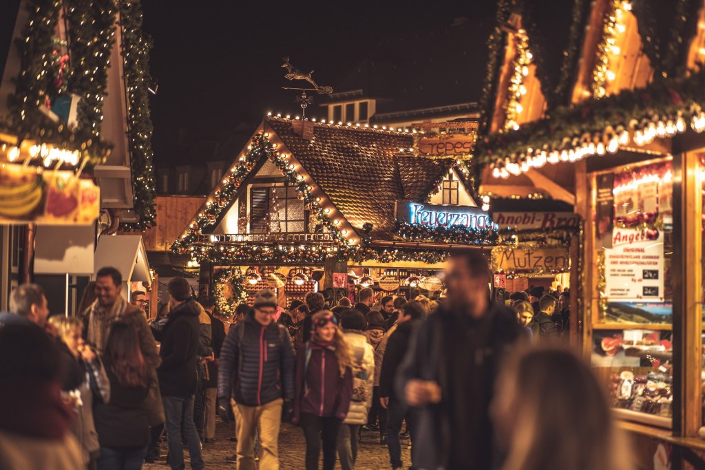 Crowds of people make their way through the rows of stalls adorned in Christmas lights in Frankfurt during the Christmas markets.