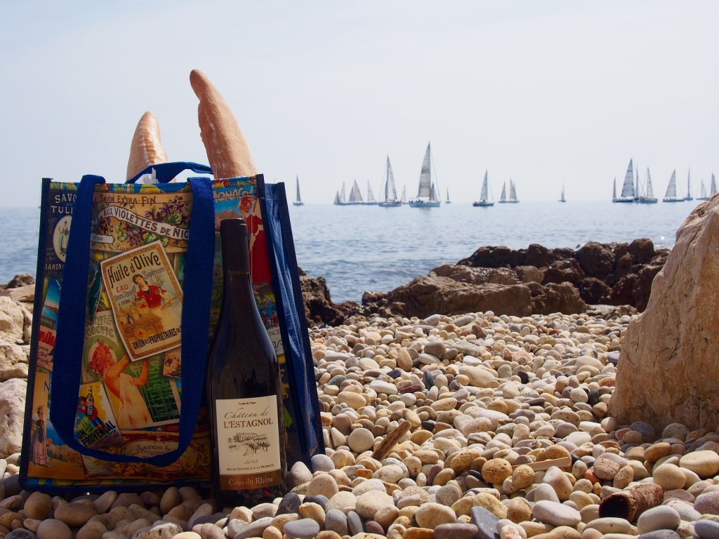 Bag with baguettes and wine on a pebble beach in France with sailboats in the background.