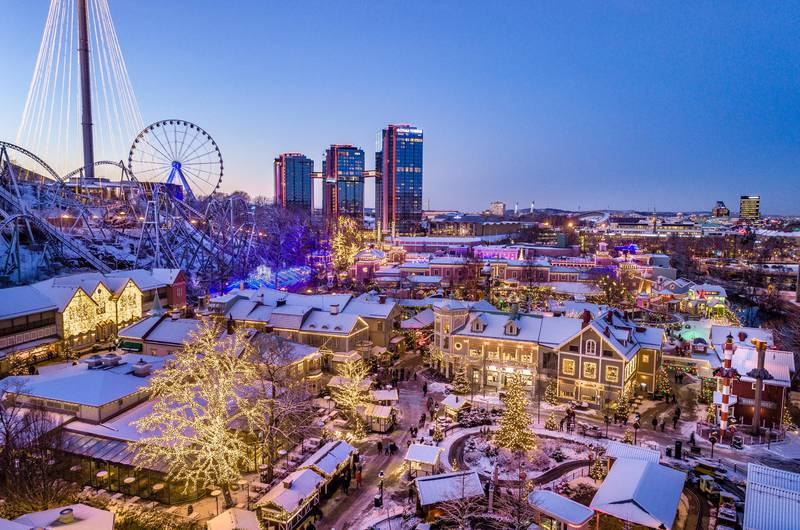 One of the many Christmas markets in Gothenburg, Sweden seen from above.  There is a light blanket of snow, many Christmas lights, and a ferris wheel in the background.