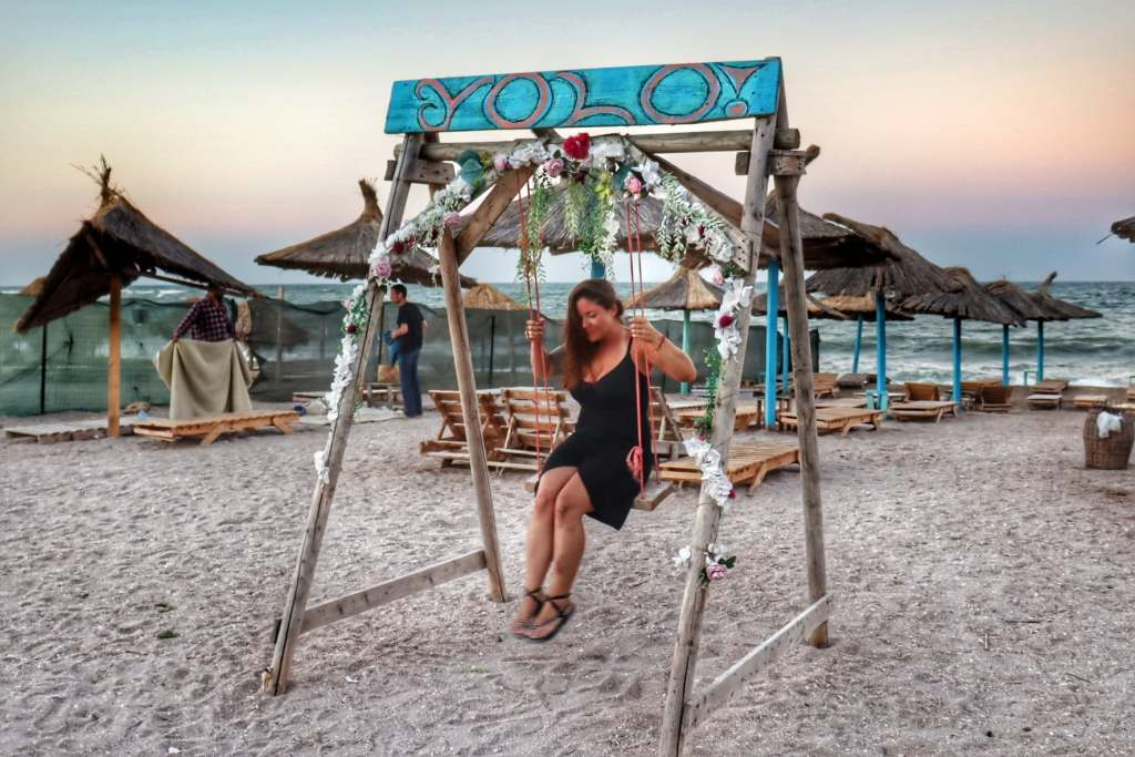 Woman on a swing on the beach in Vama Veche, Romania with the word 'YOLO' above her on the swing.
