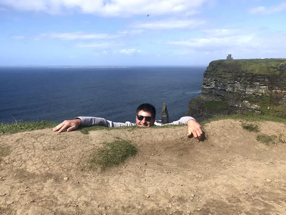 Man hanging off edge of cliff for photo opp