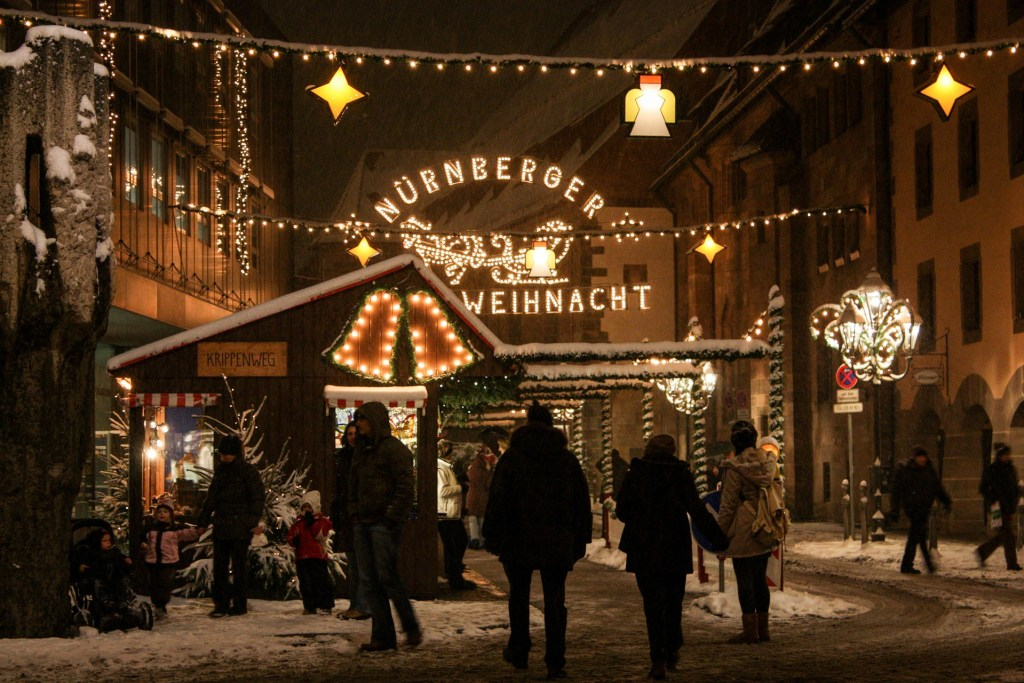 Nuremberg Christmas market at night, people walking through the snow.  There are strung lights and signs lit up in German.
