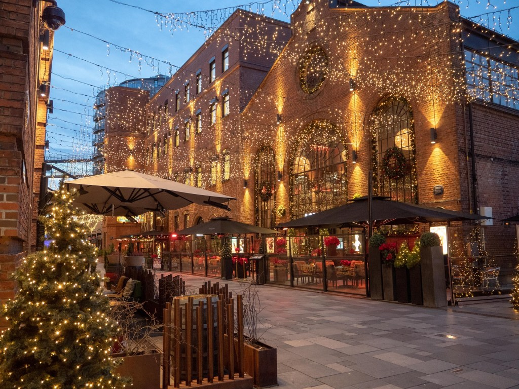 Thousands of strung lights hang between buildings in Oslo, Norway to decorate the Christmas markets.  There are wreaths and Christmas trees.