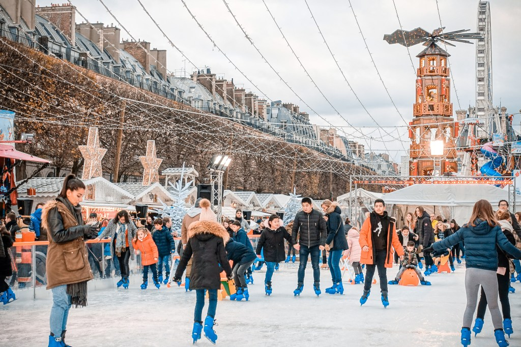 Many people ice skating at Jardin des Tuileries  in Paris during the annual Christmas market.