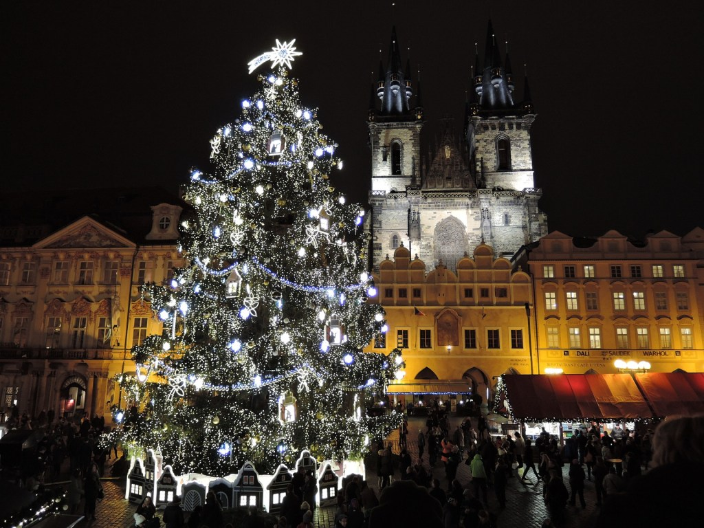 Large lit-up Christmas tree in Prague during the city's Christmas festivals.  People crowd outside the stalls to purchase from vendors.
