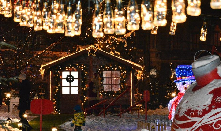 A lit up cottage with snow and Christmas decorations at night in Sarajevo.