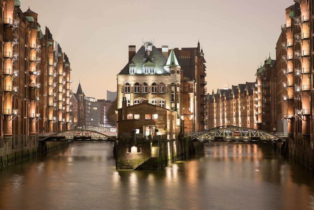 The Speicherstadt in Hamburg, illuminated with pale golden lights reflected on the river.