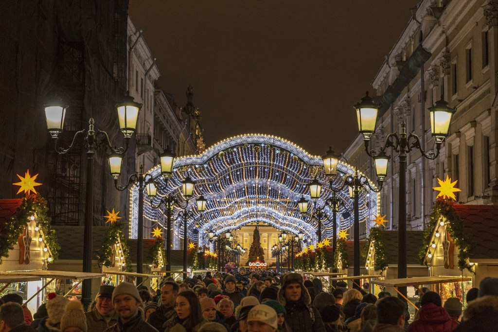 Many people crowd a dark street in St. Petersburg lined with stalls for the holiday market.