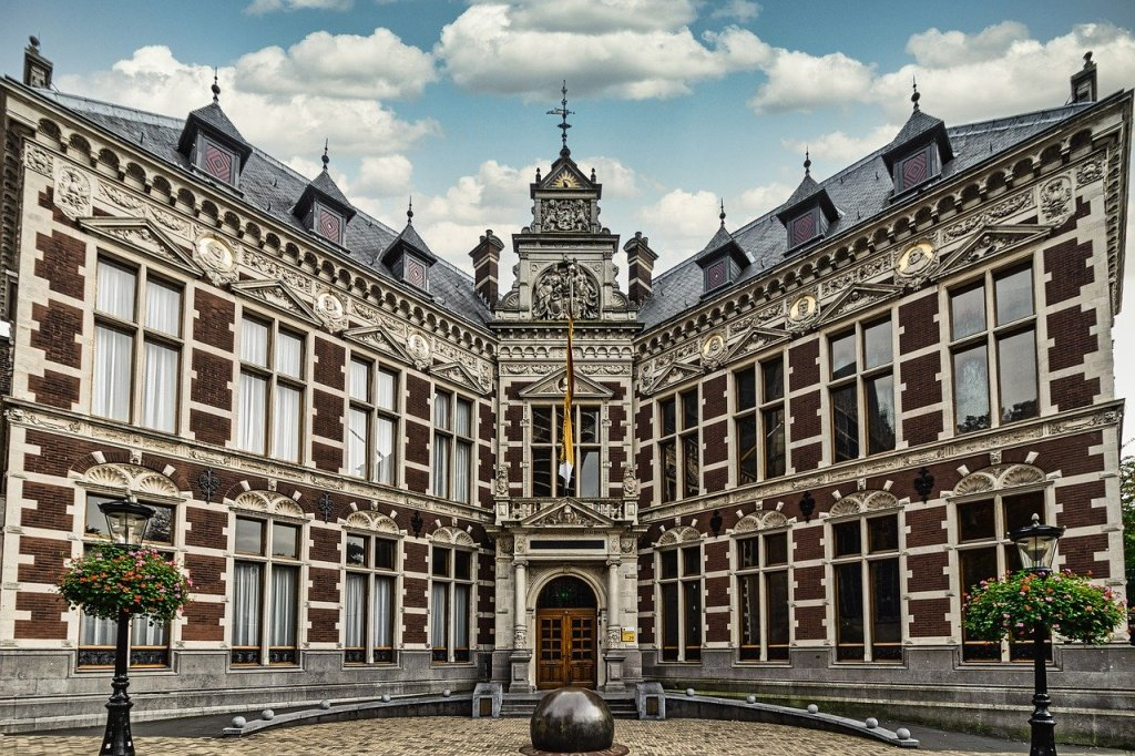 Corner courtyard of Utrecht University in Utrecht, Netherlands.  There are many geometric windows and an intricate door and front facade.