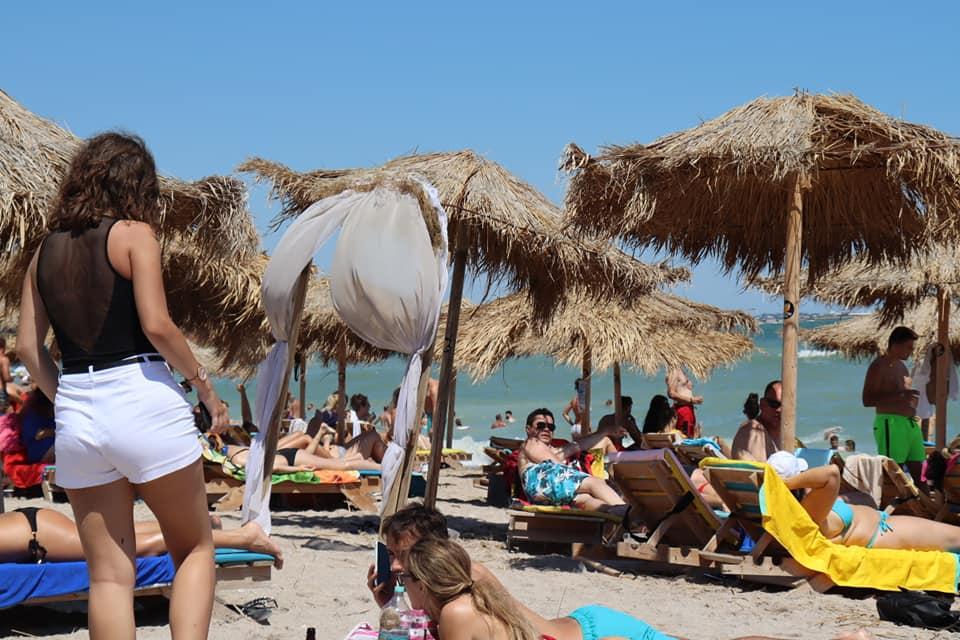 People laying on beach under straw umbrellas, Vama Veche