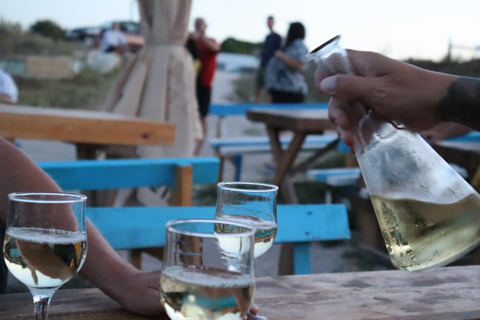 Hand outstretched pouring white wine from a carafe on the beach.