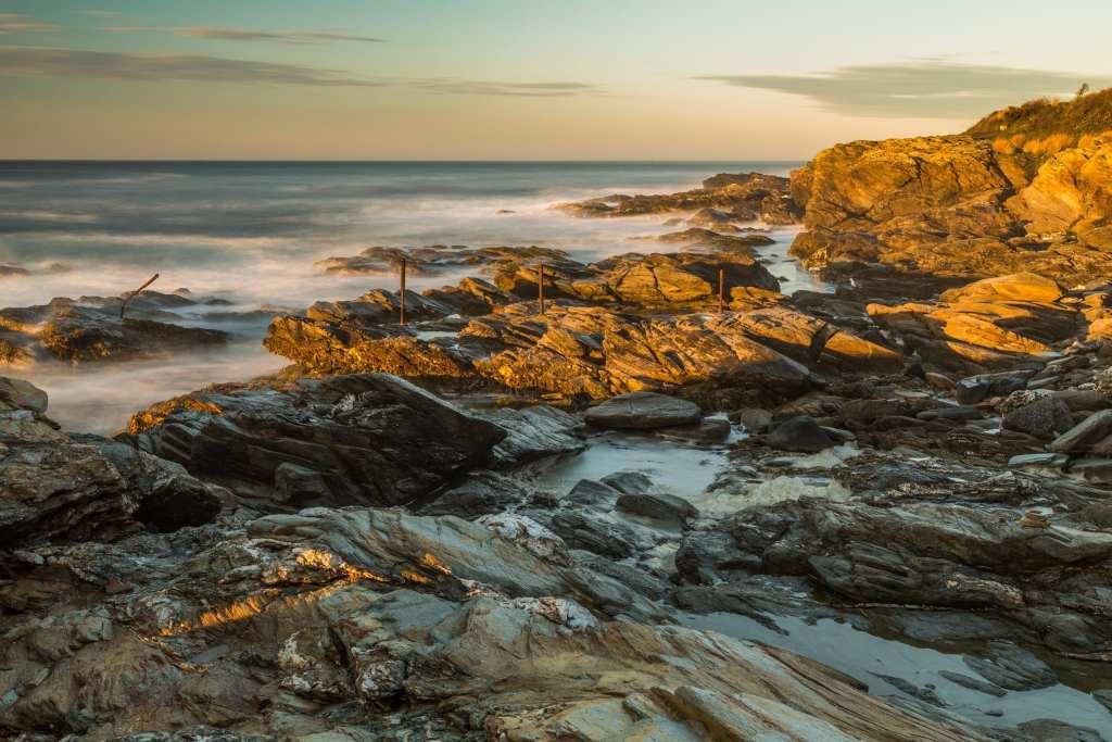 Beavertail State Park, water washing up on rocks in Rhode Island, USA during sunset.