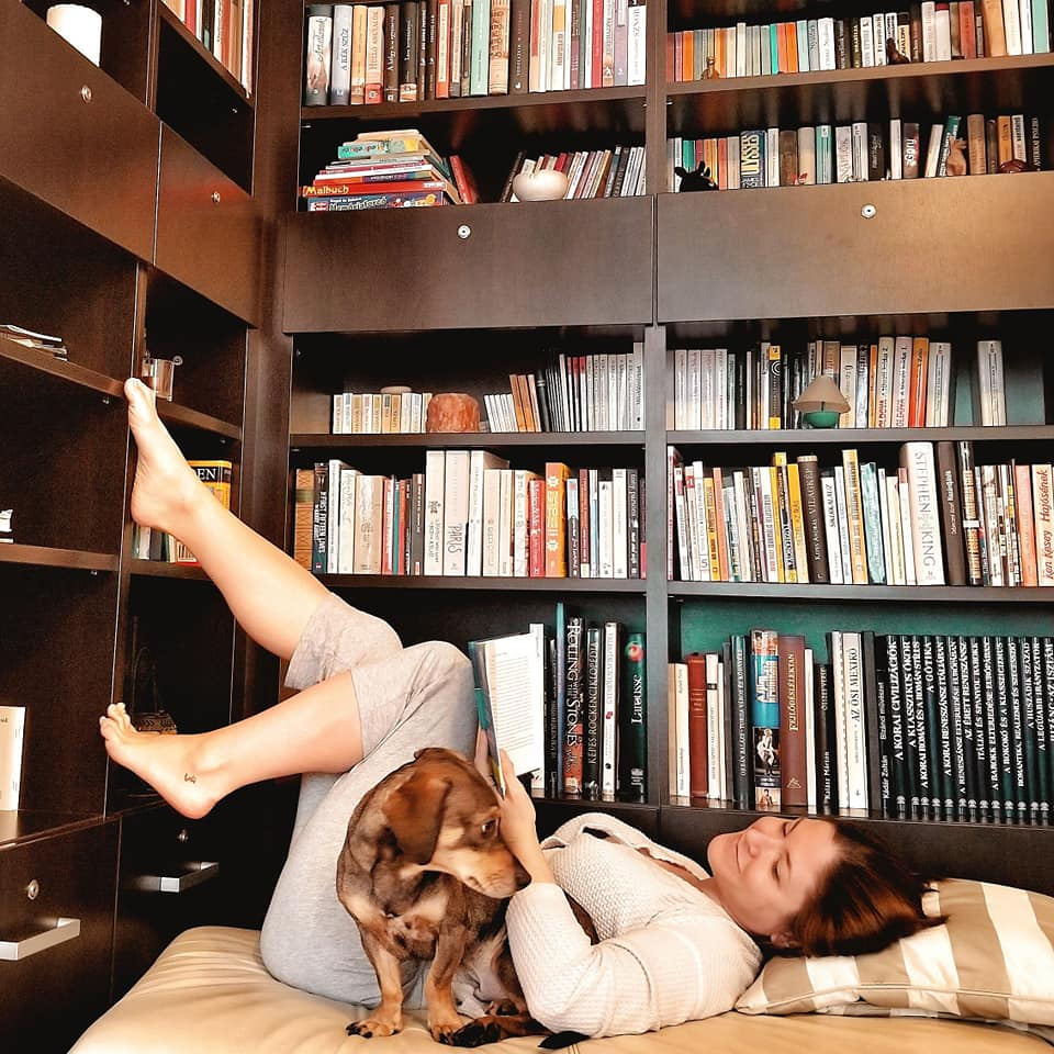 Woman and dog sitting in Budapest apartment library.