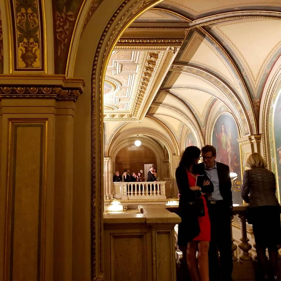 Photo from the Vienna State Opera of a couple talking to each other very close with their heads bowed toward one another.  She is in a red dress and they are standing next to the balcony.