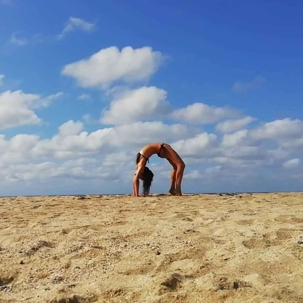 Woman doing wheel pose on a beach (backbend).