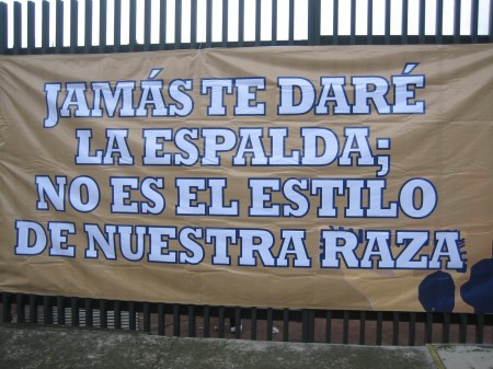 "Pumas haven't exactly been doing well this year, so this sign -- tacked onto a gate in front of the stadium -- basically means: ""Don't worry Pumas! We won't turn our back on you!"""