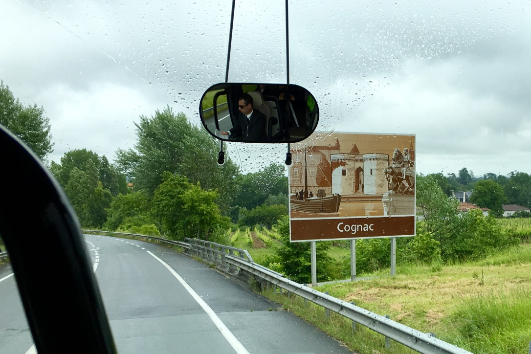 The artistic Cognac, France, welcome road sign features a colorful illustration of the old town.