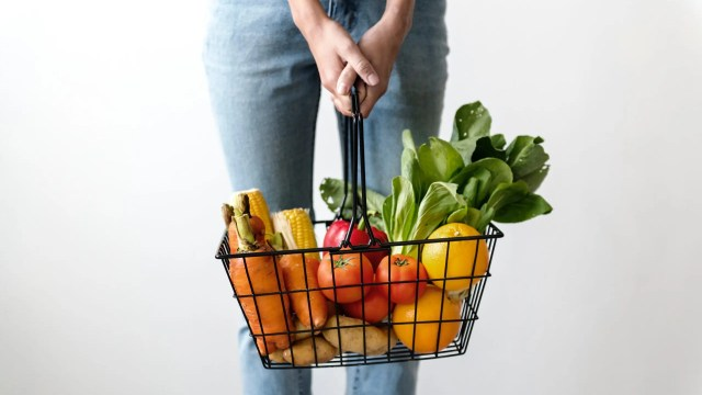 Woman holding a basket of fresh fruit and vegetables