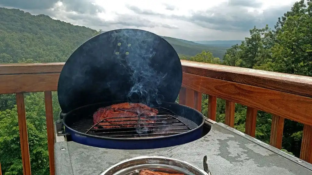 smoking beef brisket on the grill with the mountains in the background