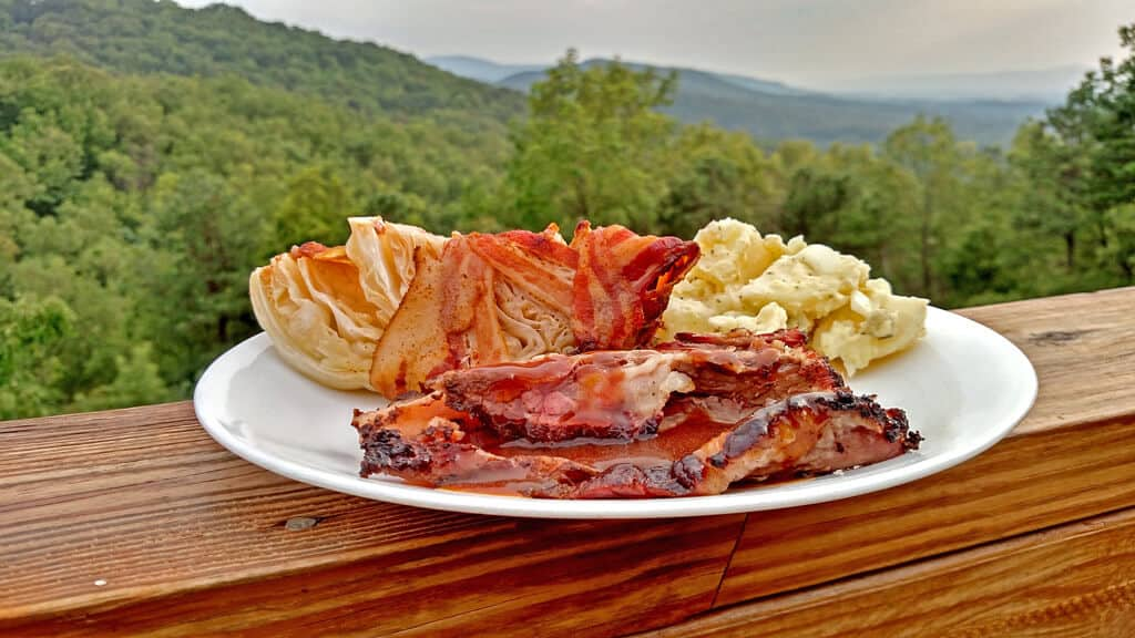 a plate of brisket and sides with the mountains in the background