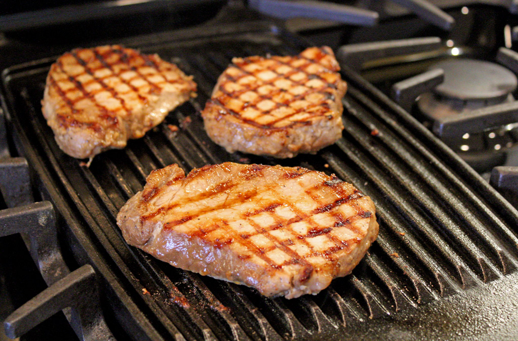 Easy to make these pork chops are full of flavor, marinated in a teriyaki sauce, made of made with soy sauce, rice vinegar, garlic, fresh ginger and sugar, overnight, enhanced by grilled flavor accompanied with stir fried vegetables and rice. | TheMountainKitchen.com