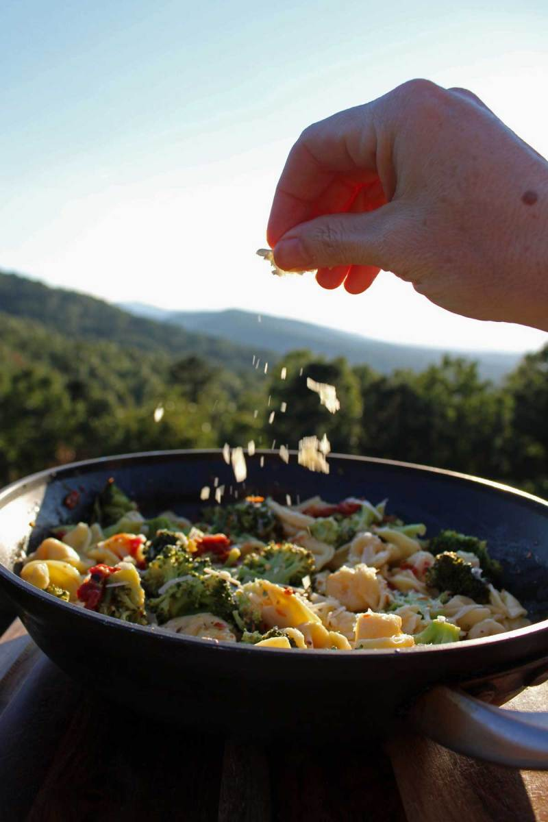sprinkling parmesan cheese into the pan with the mountains in the background