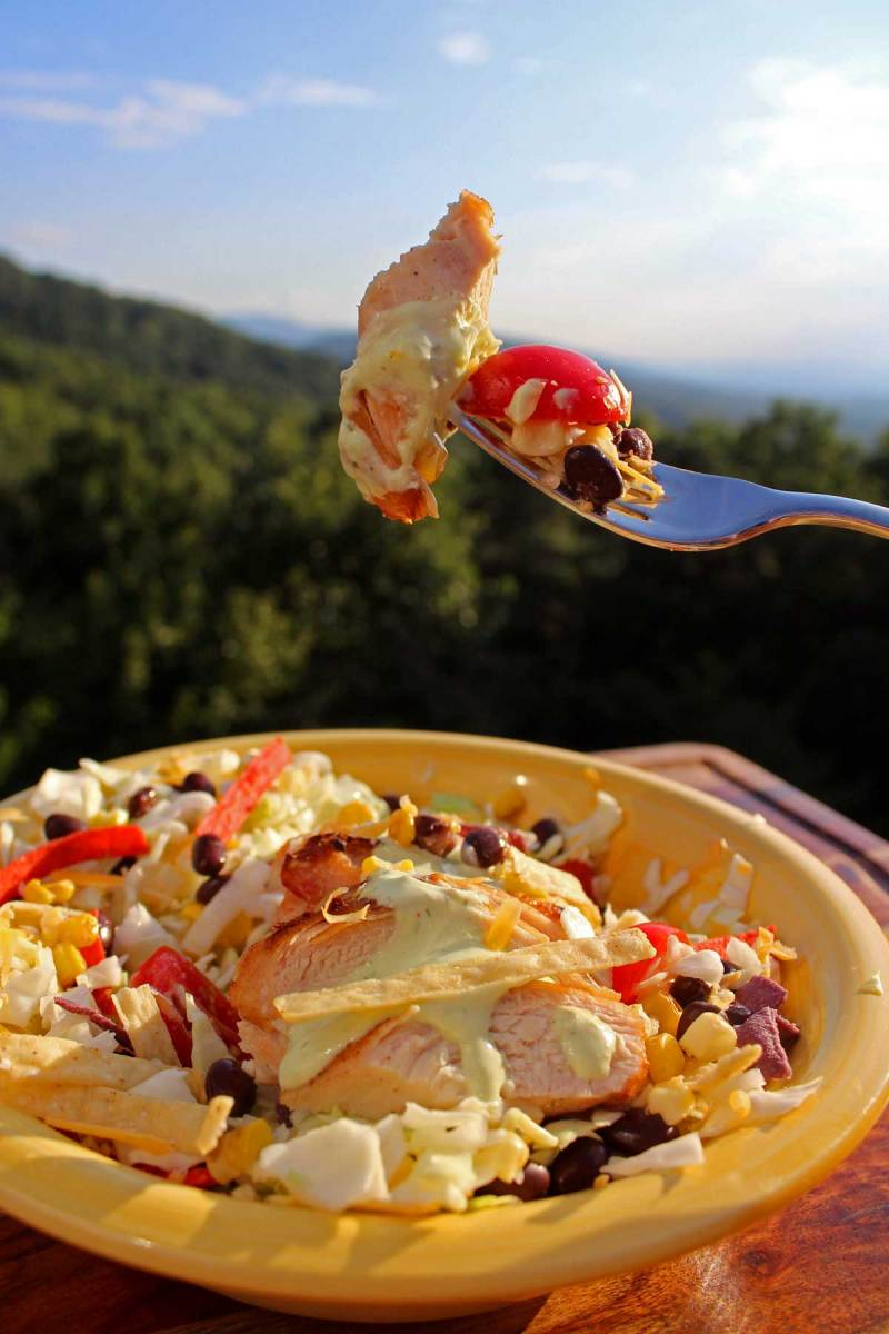 a bite of Santa Fe Salad on fork with mountain view
