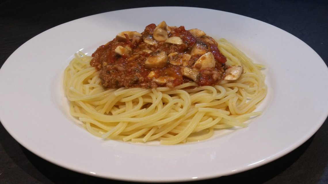 Final image of sausage bolognese on plate on top of spaghetti