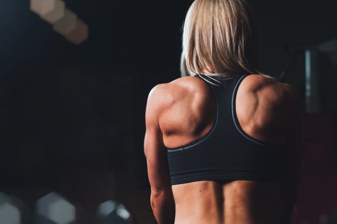 woman strength training with back to camera showing off back muscles