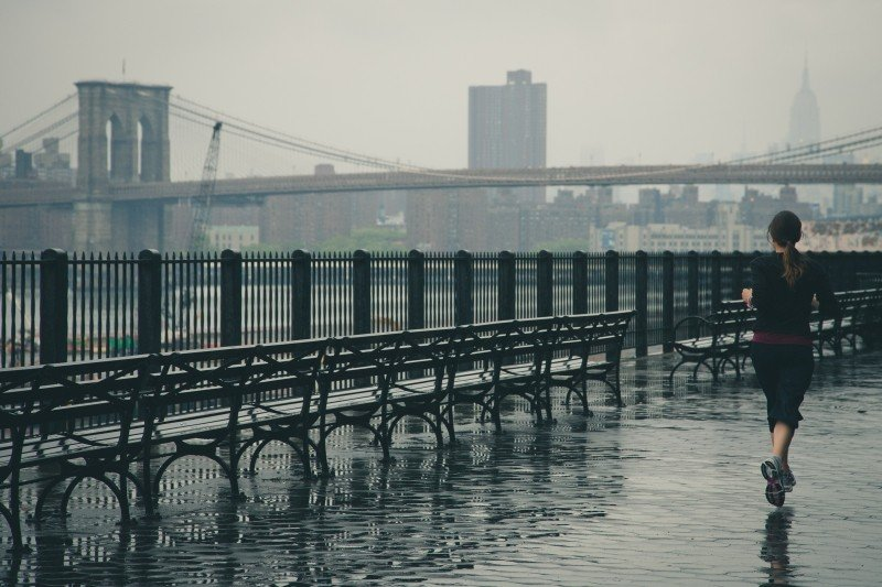 women running in the rain alongside a row of benches with a bridge in the background on a gloomy day - Try different types of running - Ways to enjoy running