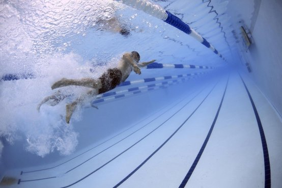 swimmer swimming a race - justify using the benefits of swimming
